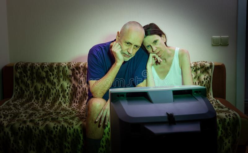 A couple of adult lovers, sitting on a couch watch movie on television stock image