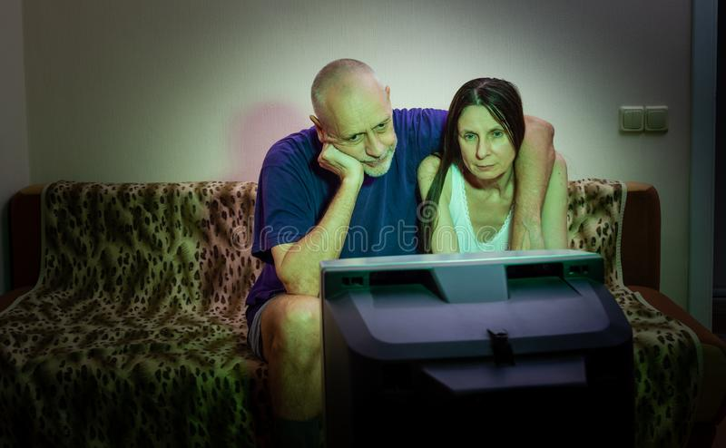 A couple of adult lovers, sitting on a couch watch movie on television royalty free stock photography