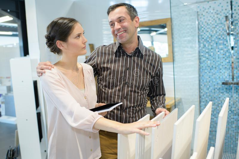 Couple adults choosing ceramic tile for bathroom stock image