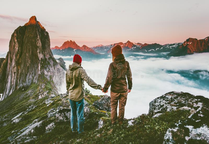 Couple adventurers hands holding traveling in Norway. Mountains healthy lifestyle concept active vacations outdoor hiking Segla together enjoying sunset royalty free stock photos