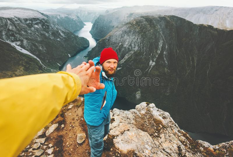 Couple adventurers in mountains follow helping hand traveling together. Lifestyle concept extreme vacations adventure weekend getaway in Norway royalty free stock photo