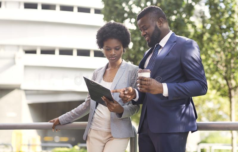 Couple of african american business partners working while standing outdoors. Men drinking coffee. Copy space stock image