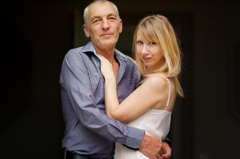 Couple with Age Difference Hugging on Black Background. Attractive Young Woman in Dress and Senior Man in Blue Shirt. Embracing and Looking at the Camera stock images
