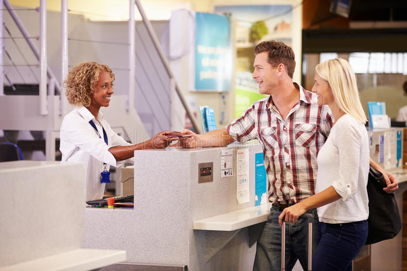 Couple At Airport Check In Desk Leaving On Vacation royalty free stock photo