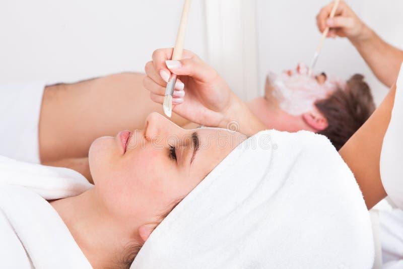 Couple applying facial mask stock photography