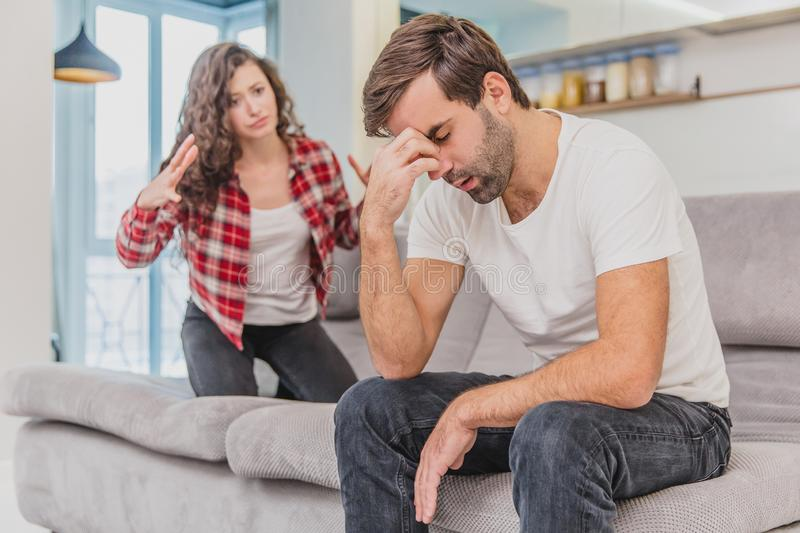 Couple argue. The wife shouted to her desperate husband, sitting on the couch in the living room at home. A man does not. Couple argue. The wife shouted to her royalty free stock photography