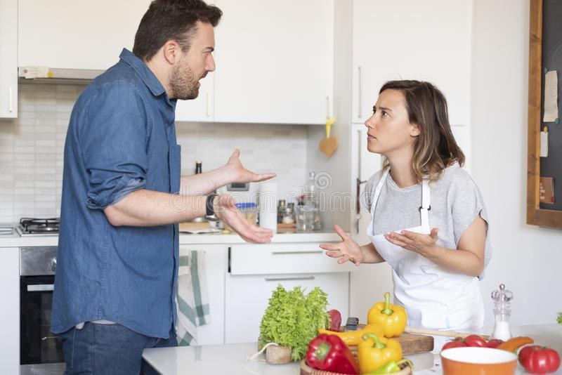 Relationship difficulties during the food preparation. Couple arguing about cooking at home in the kitchen royalty free stock images