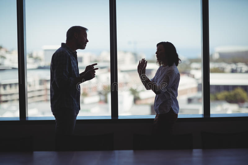 Couple arguing near the window. In office royalty free stock photo