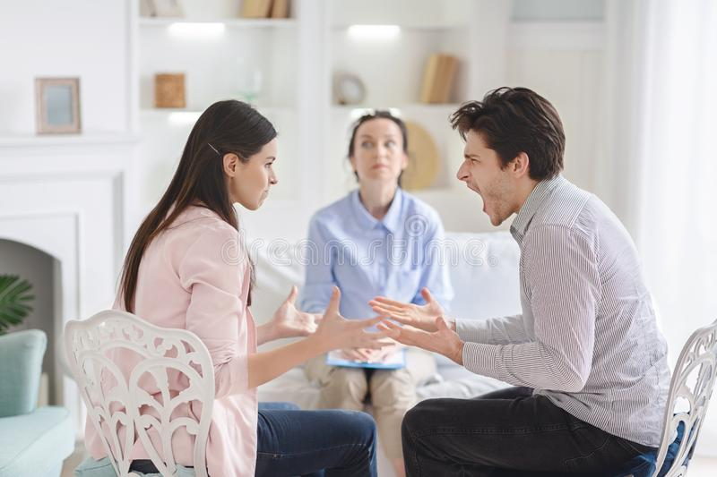 Couple arguing during therapy session with psychologist. Consulting family relationships expert or marriage counselor, free space royalty free stock photo