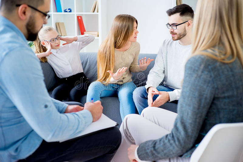 Couple arguing at therapy session in therapists office. Unhappy couple arguing at therapy session in therapists office royalty free stock image