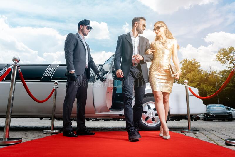 Couple arriving with limousine walking red carpet stock photos