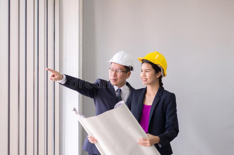 Couple asian foreman hand pointing at working expertising the structureon construction site with blue print,Selective focus. Couple asian foreman hands pointing royalty free stock images