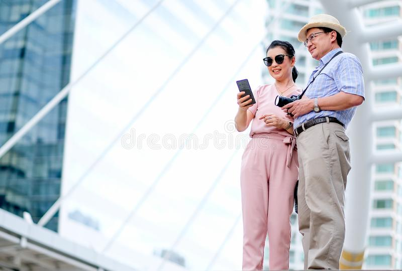 Couple of Asian old man and woman tourist are looking at mobile phone and smiling. This photo also contain concept of good life of stock image