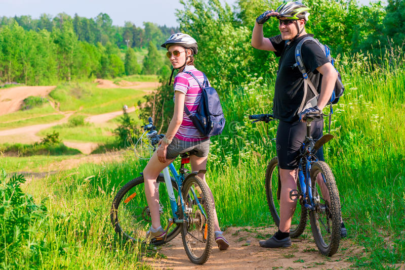 Couple athletes on the mountain bike resting. On a hill stock photography