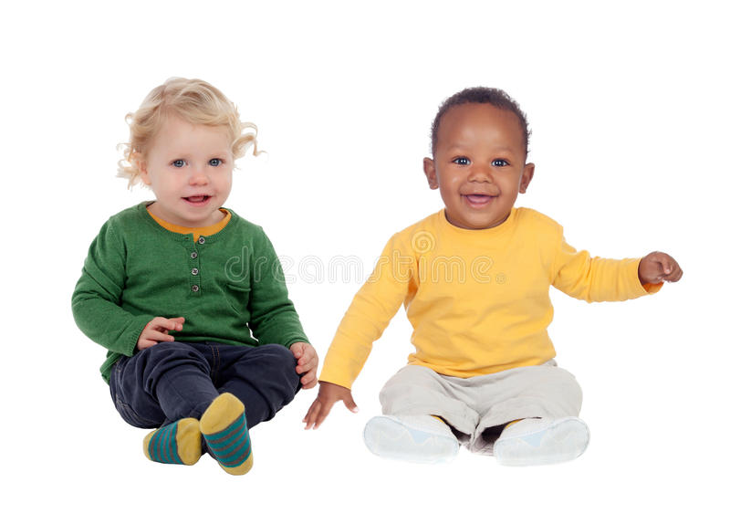 Couple of babies sitting on the floor. Isolated on a white background stock photography