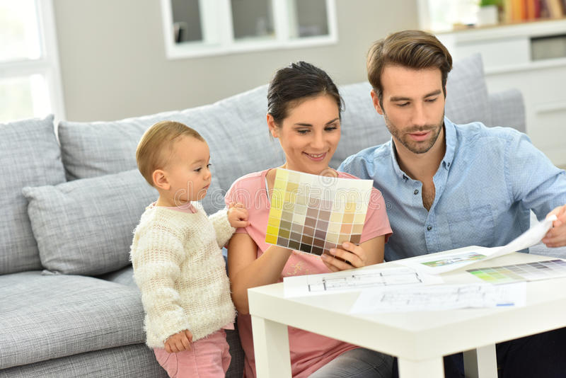 Couple with baby choosing paint color for their house royalty free stock image