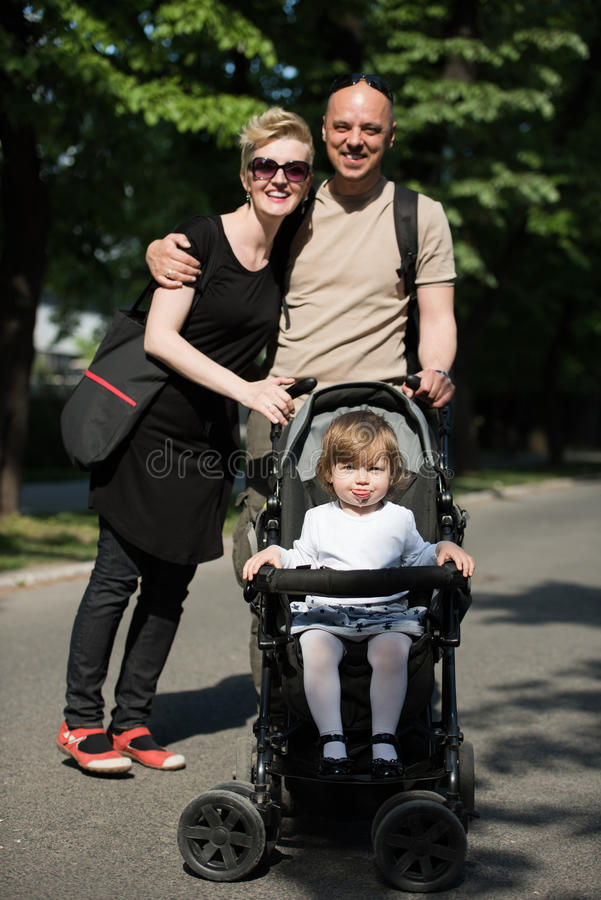 Couple with baby pram in summer park stock photo