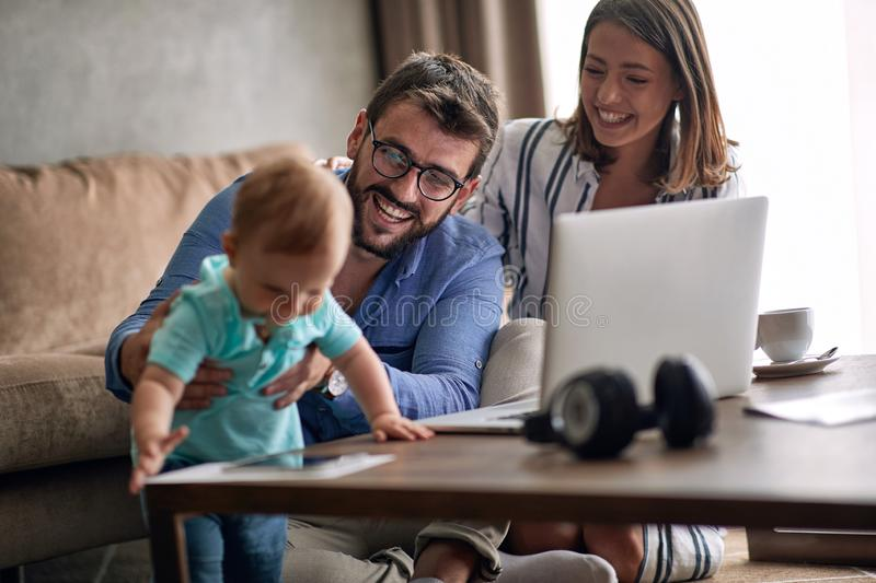 Couple with baby working from home using laptop stock image
