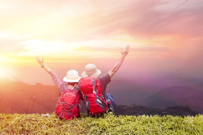 Couple backpack enjoying sunset on peak of foggy mountain royalty free stock image