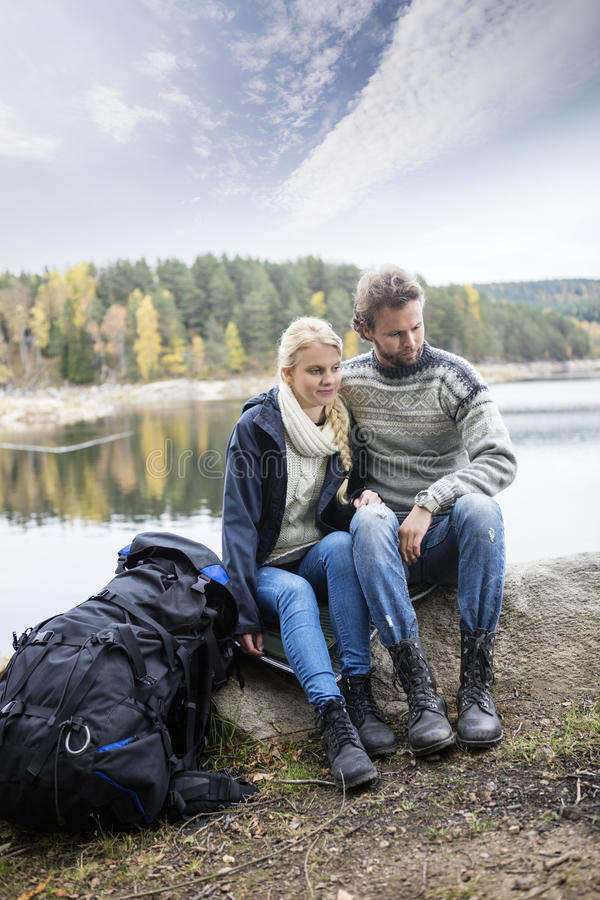 Couple With Backpack Relaxing On Lakeshore During Camping royalty free stock photos