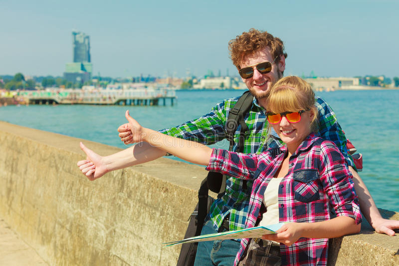 Couple backpacker with map by seaside hitchhiking. Adventure, summer, tourism. Young couple backpacker hitchhiker with map by seaside hitchhiking with thumb up royalty free stock images