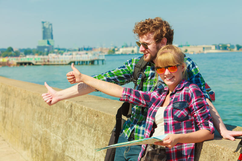 Couple backpacker with map by seaside hitchhiking. Adventure, summer, tourism. Young couple backpacker hitchhiker with map by seaside hitchhiking with thumb up royalty free stock photography