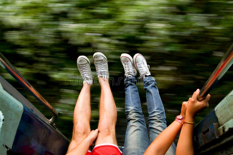 Young backpackers couple traveling and living adveture trip exploring asia by train with legs out of fast moving train. Couple of backpackers exploring in fast stock images