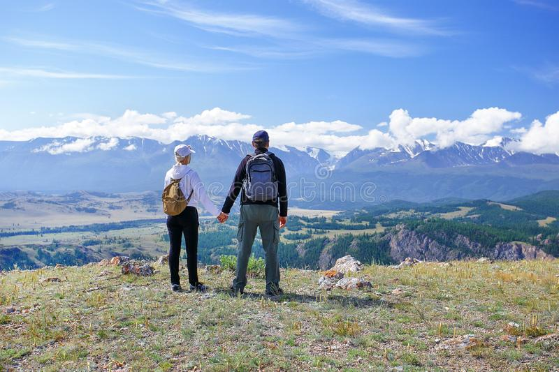 Couple backpackers holding hands enjoying mountains. stock photos