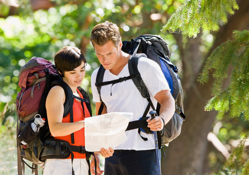 Couple with backpacks and map. Couple with backpacks looking at map