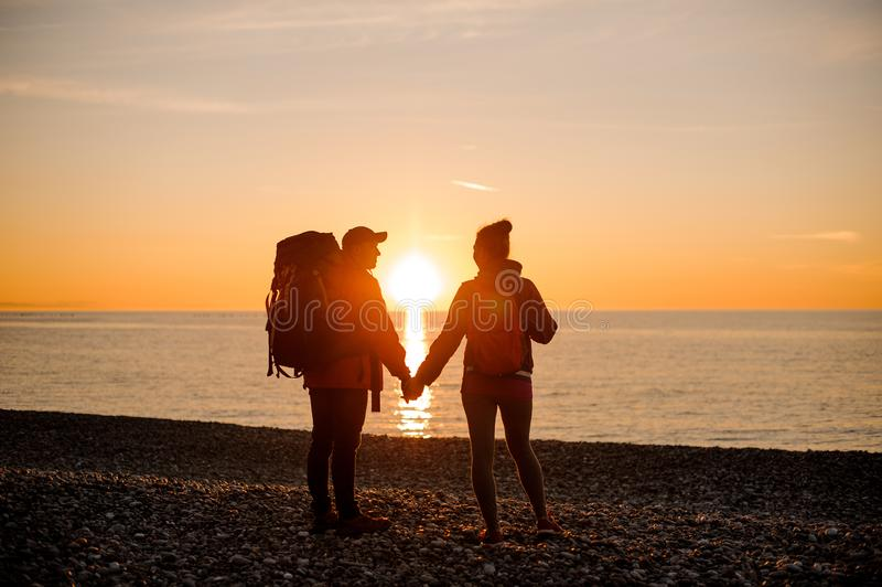 Couple with a backpacks standing near the sea and looking into each other eyes stock photography