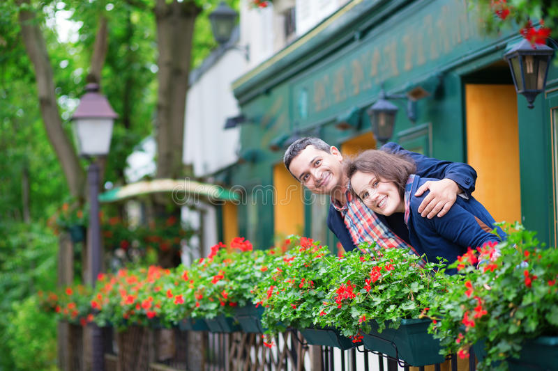 Couple on balcony with blossoming geranium. Looking cheerfully at camera royalty free stock images