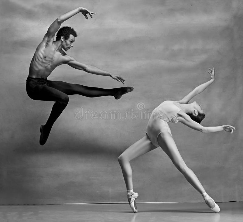 Couple of ballet dancers posing over gray background royalty free stock image