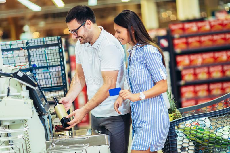 Couple with bank card buying food at grocery store or supermarket self-checkout royalty free stock photography