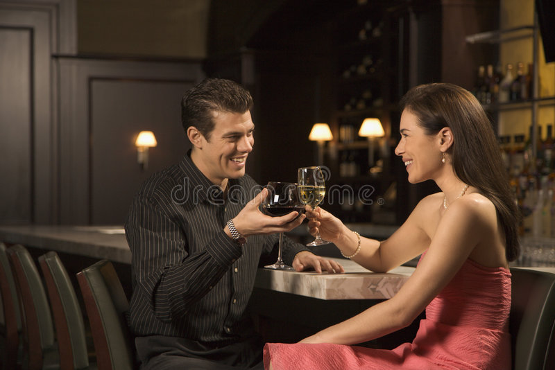 Couple at bar. Mid adult Caucasian couple at bar toasting wine glasses and smiling stock photo