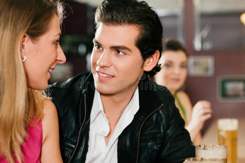 Couple in bar drinking beer flirting royalty free stock image