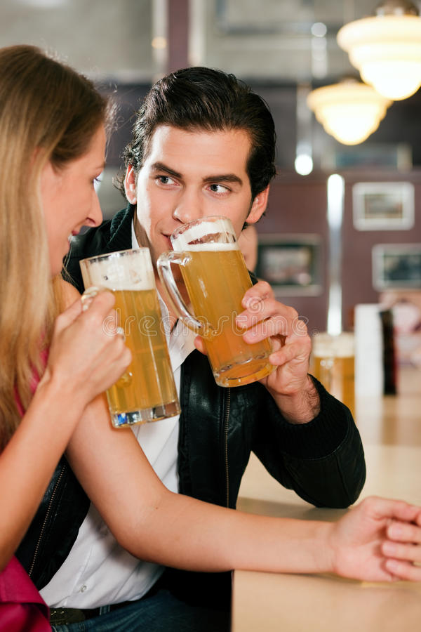 Couple in bar drinking beer flirting. Group of people in a bar or restaurant drinking beer, one couple flirting very obviously having a lot of fun royalty free stock images