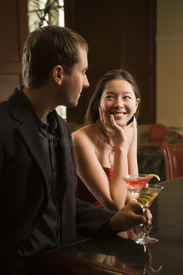 Couple at bar with drinks. royalty free stock images