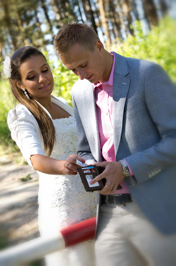 Couple at barrier gate with wallet. Couple standing at barrier gate removing money from wallet royalty free stock image