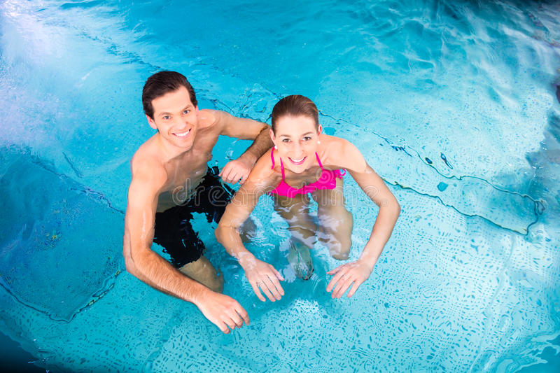 Couple bathing in swimming pool stock image
