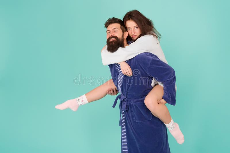 Couple in bathrobes having fun turquoise background. Lets stay at home and have fun. They always have fun together. Close relationship. Handsome young men stock images