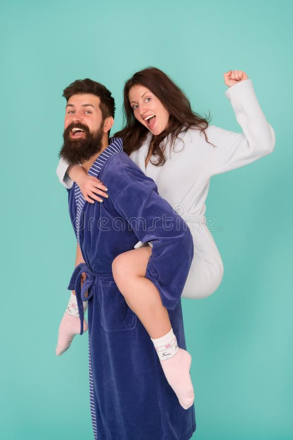 Couple in bathrobes having fun turquoise background. Lets stay at home and have fun. They always have fun together. Enjoying every second together. Handsome royalty free stock images