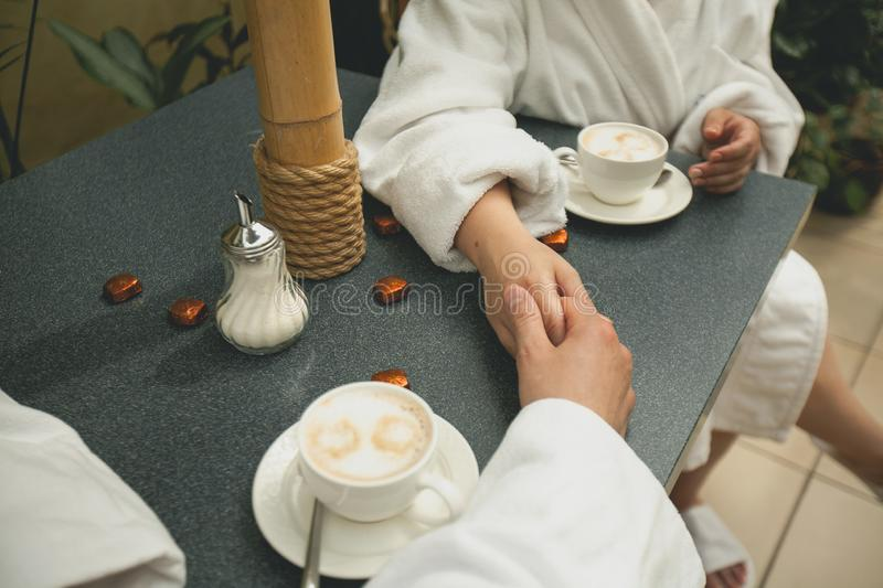 A couple in bathrobes holding hands, drinking coffee while relaxing in the Spa, close-up. Hands of lovers on the background of a stock photos