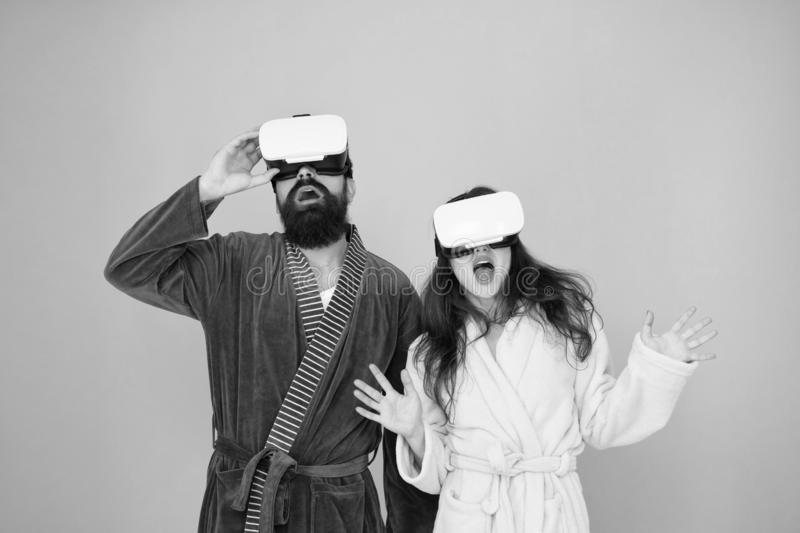 Couple in bathrobes wear vr glasses. Conscious awakening. Return to reality. Man and woman explore vr. VR technology and. Couple in bathrobes wear vr glasses stock photography