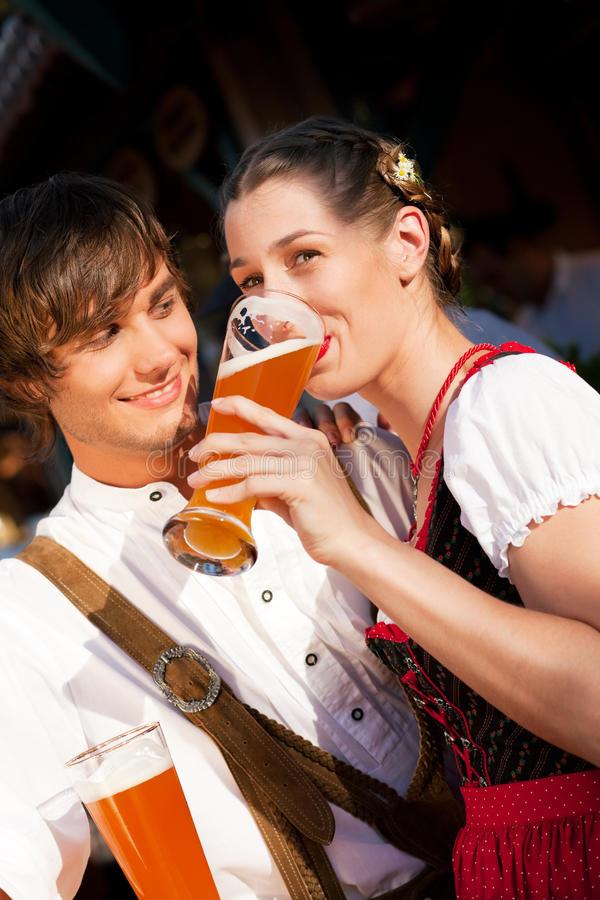 Couple in Bavarian Tracht drinking wheat beer. Couple in traditional Bavarian Tracht - Dirndl and Lederhosen - in a beer tent at the Oktoberfest or in a beer royalty free stock images