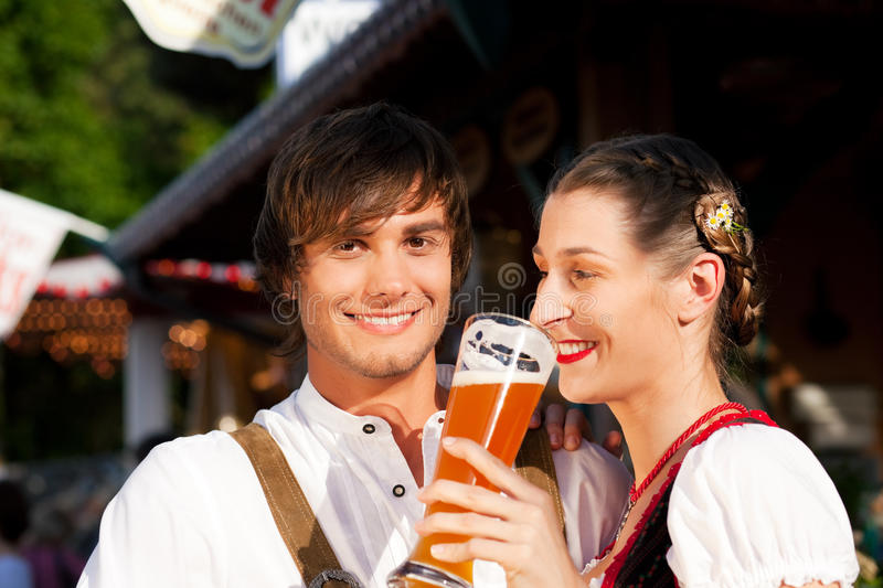 Couple in Bavarian Tracht drinking wheat beer. Couple in traditional Bavarian Tracht - Dirndl and Lederhosen - in a beer tent at the Oktoberfest or in a beer royalty free stock photography
