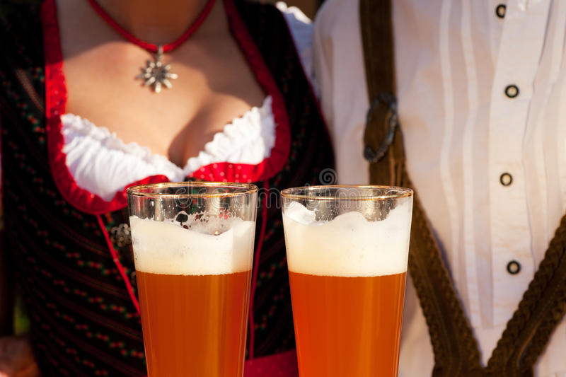 Couple in Bavarian Tracht drinking wheat beer. Couple in traditional Bavarian Tracht - Dirndl and Lederhosen - in a beer tent at the Oktoberfest or in a beer royalty free stock photos