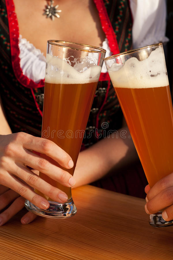 Couple in Bavarian Tracht drinking wheat beer. Couple in traditional Bavarian Tracht - Dirndl and Lederhosen - in a beer tent at the Oktoberfest or in a beer stock images