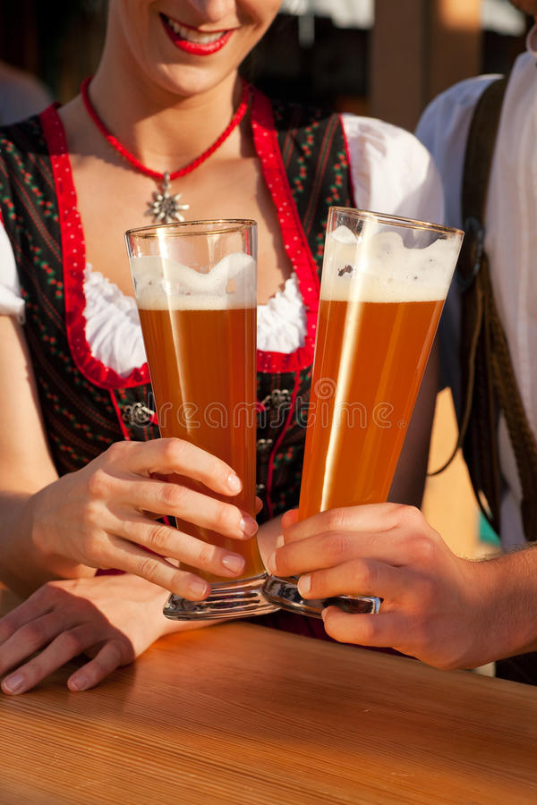 Couple in Bavarian Tracht drinking wheat beer. Couple in traditional Bavarian Tracht - Dirndl and Lederhosen - in a beer tent at the Oktoberfest or in a beer stock photo