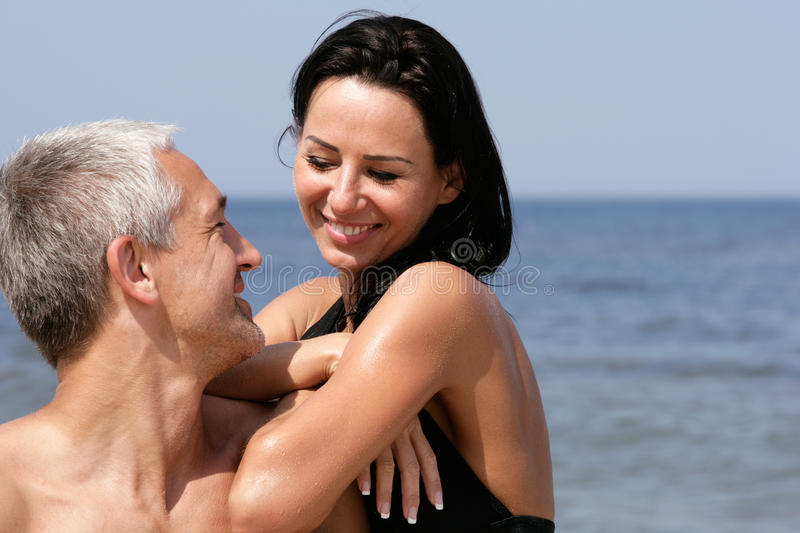 Couple on the beach. Attractive mature couple relaxing on the beach royalty free stock photo