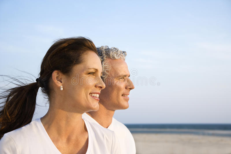 Couple on Beach. Side view of smiling middle aged couple on beach looking off into the distance together. Horizontal shot royalty free stock photo